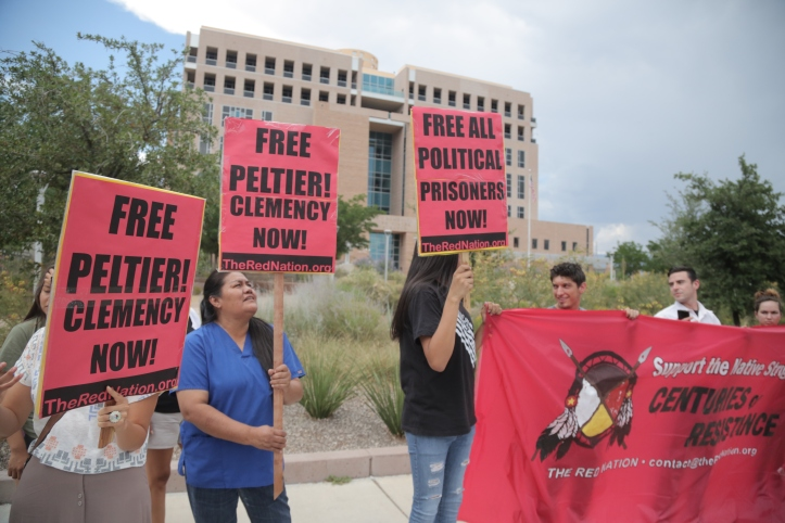 """Peltier supporters held signs that read """"Free Peltier, Clemency Now"""" and """"Free All Political Prisoners."""""""